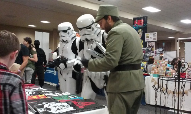Storm Troopers examining artwork made entirely from duct tape.